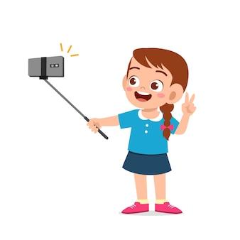 カメラの前でかわいい小さな子供の女の子のポーズと自分撮り