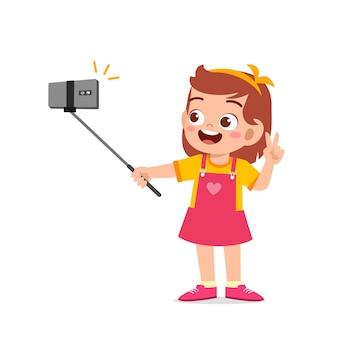 スマートフォンのイラストの前でかわいい小さな子供の女の子のポーズと自分撮り