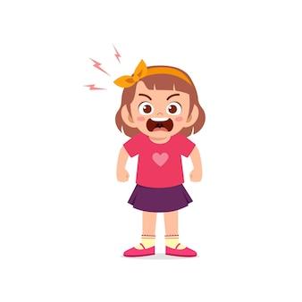 Милая маленькая девочка стоит и показывает выражение сердитой позы
