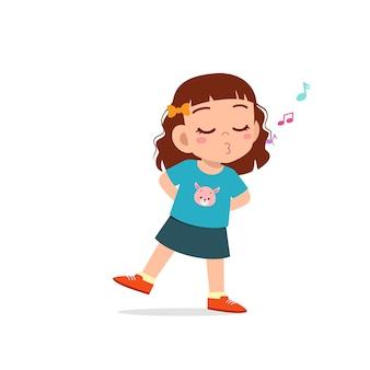 Милая маленькая девочка ребенка стоит и насвистывает ртом
