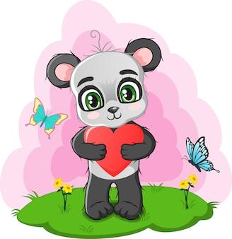 赤いハートを持っているかわいい小さなパンダ