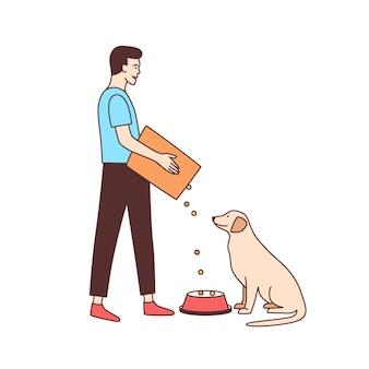 動物保護施設またはポンドで野良犬に餌をやるかわいい男性ボランティア。若い男が分離したホームレスまたは放棄された犬に食べ物を与える
