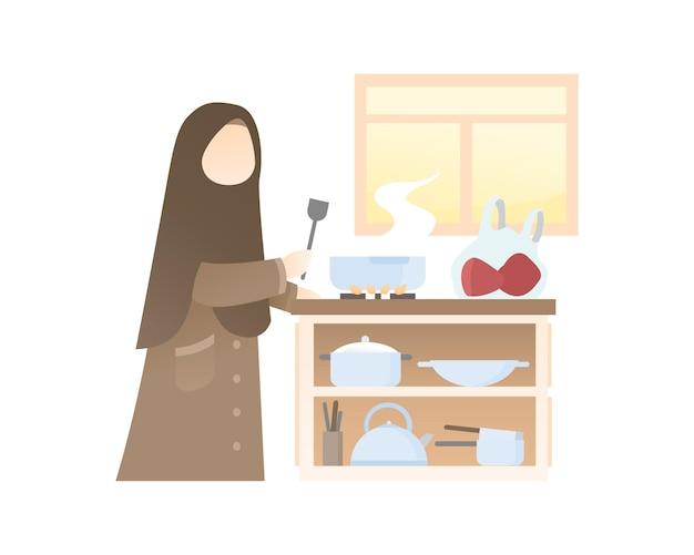 キッチンで料理をするかわいいイスラム教徒の少女