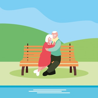 Cute old couple seated in chair of park