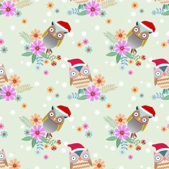 かわいいフクロウは花のシームレスなパターンでブランチにクリスマスの帽子をかぶっています。