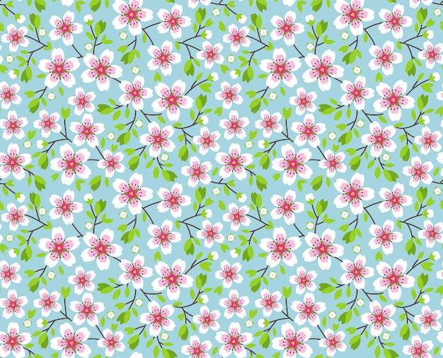 小さな花のかわいいパターン。ピンクのさくらの花、開花する日本の桜。春のシンボル。小さな色とりどりの花。青い背景。花のシームレスなパターン。小さなかわいいシンプルな春の花。