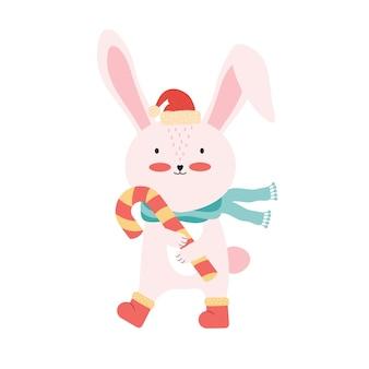 キャンディケインとサンタの帽子のかわいいピンクの赤ちゃんウサギ。分離された面白い漫画の動物