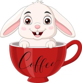 Милый кролик сидит в красной чашке