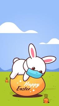 卵のステッカーの上に横たわるコロナウイルスのハッピーイースターのウサギを防ぐためにフェイスマスクを着ているかわいいウサギ