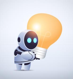 Милый робот киборг держит лампу современный робот персонаж с яркой лампочкой новый проект креативная идея технология искусственного интеллекта