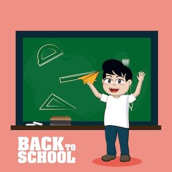 Cute school boy in front of blackboard