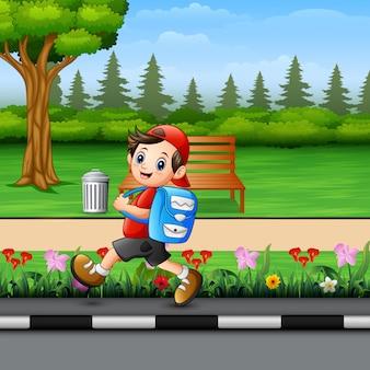 Cute school boy going to school pass through a park