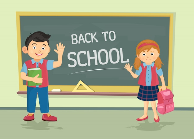 Cute schoolgirl and schoolboy wearing uniform with backpacks standing near blackboard