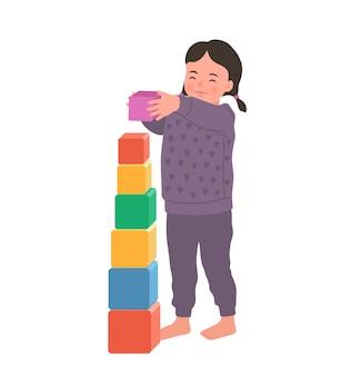 Милая улыбающаяся девушка стоит, держа красочный куб. ребенок играет развивающую игрушку. игрушки для маленьких детей