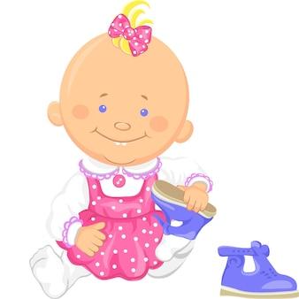 귀여운 웃는 앉아 있는 여자 아이는 샌들을 가지고 노는 신발을 신는 법을 배웁니다.