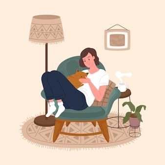 快適なソファの猫に座っているかわいい笑顔の若い女の子。ペットと一緒に家で過ごす愛らしい女性。