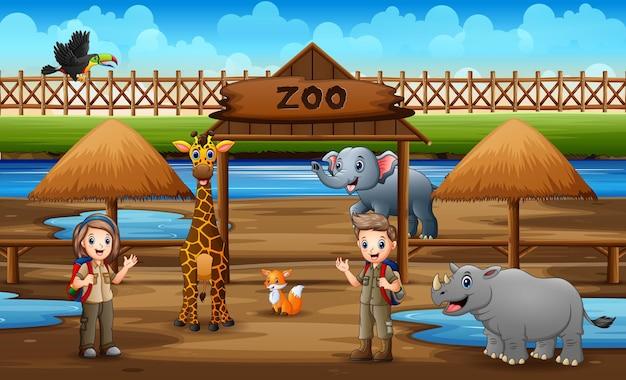 動物園の公園で動物を見ているかわいいスカウトの男の子と女の子