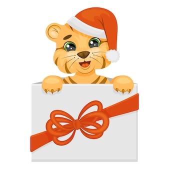 Милый тигренок в шляпе деда мороза в подарочной коробке. каваи персонаж. векторная иллюстрация детей ... векторная иллюстрация. мультяшный стиль. изолированные на белом.