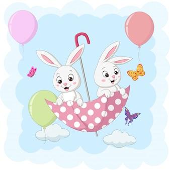 Симпатичные два кролика летают с зонтиком
