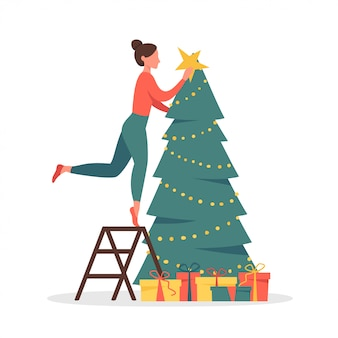 Cute woman decorating christmas tree with garlands and gold star.