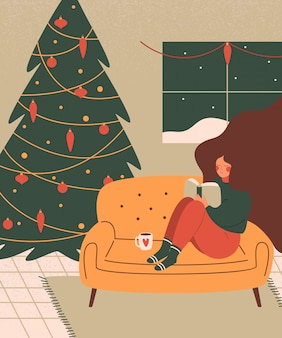 A cute woman relaxes with a book in a cozy living room decorated for christmas holiday.