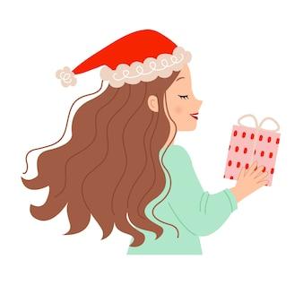 クリスマスプレゼントを持ってサンタ帽子をかぶったかわいい女性