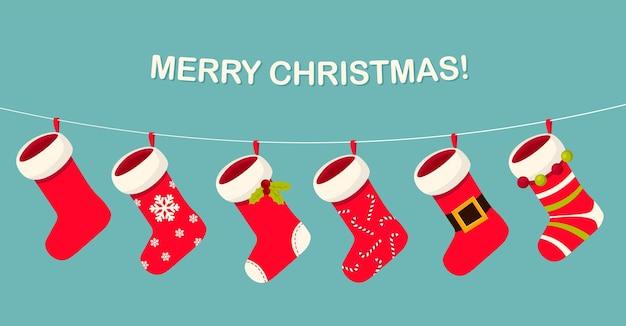 Симпатичные рождественские красно-белые носки или чулок, висящие на веревке, празднование рождества и нового года