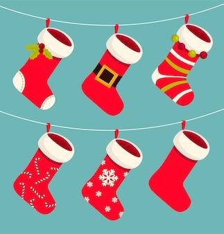 かわいいクリスマスの赤と白の靴下やストッキングがロープにぶら下がっています。クリスマスと年末年始。 Premiumベクター