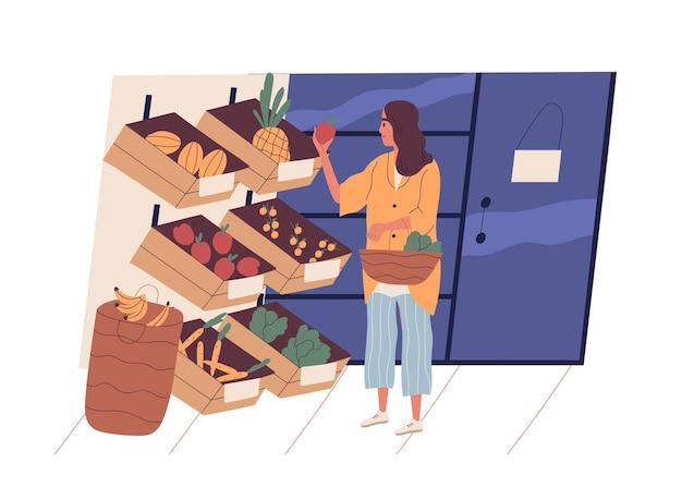 식료품가 게에서 음식을 구입하는 쇼핑 바구니와 함께 귀여운 젊은 여자. 슈퍼마켓에서 과일과 야채를 선택하는 재미있는 여자
