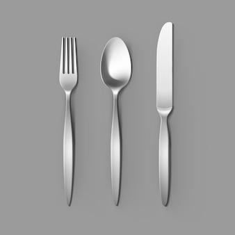 Набор столовых приборов серебряная вилка, ложка и нож изолированные, вид сверху