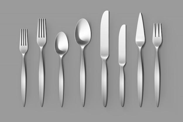 Набор столовых приборов из серебряной вилки, ложки и ножи. сервировка стола