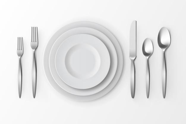 Набор столовых приборов из серебряных вилок, ложек и ножей с тарелками