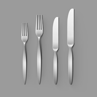 Cutlery set of silver forks and knifes isolated, top view