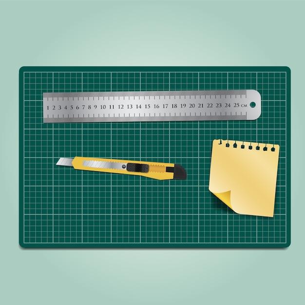 緑のカッティングマットのカッタールーラーと紙