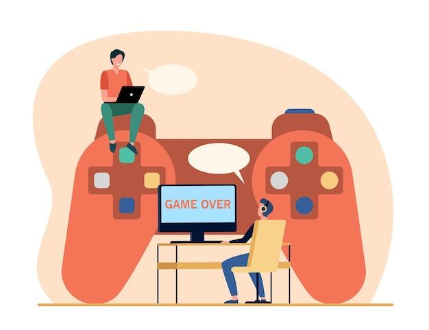 Участники соревнований по киберспорту. крошечные геймеры играют в онлайн-игру на огромном контроллере