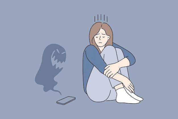 사이버 괴롭힘과 인터넷 개념에서의 학대. 어린 슬픈 우울한 소녀 만화 캐릭터는 벡터 삽화 위에 괴물이 날아다니는 스마트폰을 보고 앉아 있습니다.