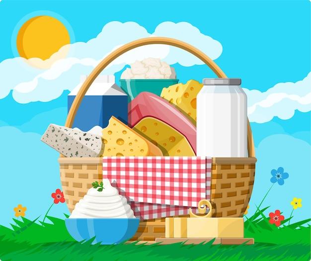 Набор молочных продуктов в корзину. сбор молочной пищи. молоко, сыр, масло сливочное, сметана, творог, сливки. природа трава цветы облако и солнце. традиционные фермерские продукты.