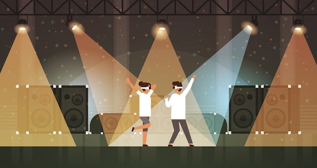 Dancers couple wearing virtual reality glasses dancing on stage with light effects disco studio musical equipment multimedia speaker