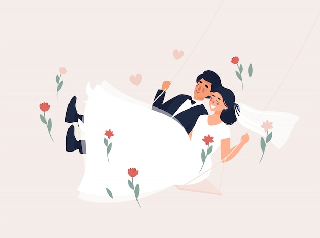 Dark-haired bride and groom swinging on a swing with flowers