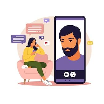 出会い系アプリ、アプリケーションまたはチャットの概念。女性はソファに大きなスマートフォンを持って座って電話で話している。