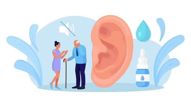 手のジェスチャーで話している聴覚障害者。大きな耳とミュートサインの近くに障害のある高齢者。手話と難聴とのコミュニケーション