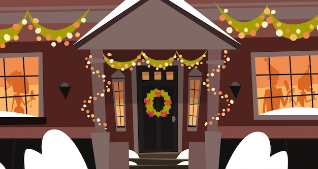 Decorated house front door with wreath winter holidays building, merry christmas and happy new year concept