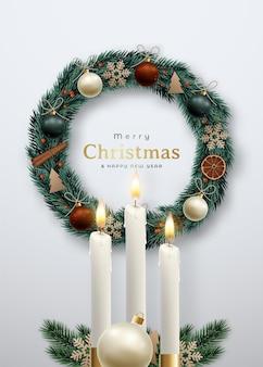 Декоративный рождественский венок и зажженные свечи на фоне серой стены