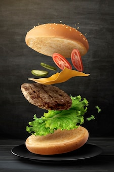 Delicious hamburger flying in the air on blackboard background in 3d illustration