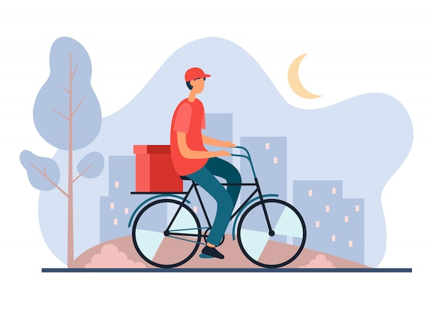 Delivery worker riding bicycle in city late at night