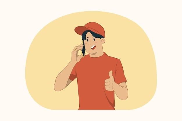 配達の若い男は携帯電話を持って親指を立てるジェスチャーの概念
