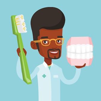 Стоматолог с зубной моделью челюсти и зубной щеткой.