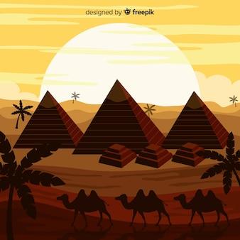 Пейзаж пустыни с пирамидами и караваном