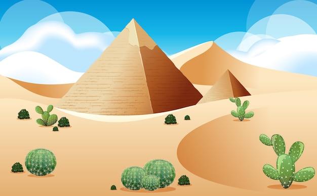 日中のシーンでピラミッドとサボテンの風景と砂漠