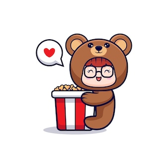 クマの衣装を着てかわいい女の子のデザインは大きなポップコーンを抱きしめます